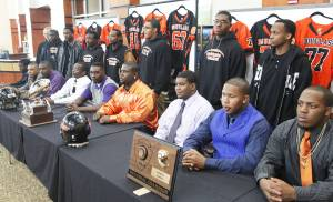 Other senior football players pose with the players signing to play college football during Wednesday's ceremony at Douglass High School. Photo by David McDaniel, The Oklahoman