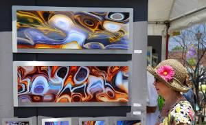 A woman passes artwork by 'new media artist' Barry Reithmeier from Rockford, IL. The forecast of  storms and rain for the latter part of the Memorial Day holiday weekend brought large crowds taking advantage of Saturday's sunshine-filled sky to the 40th annual Paseo Arts Festival on Saturday, May 28, 2016. The festival, held in the historic Paseo Arts District, NW 30 and Dewey, in Oklahoma City, is one of the biggest arts festivals of the year in Oklahoma with many different types of art on display and for sale including photography, paintings, wood pieces, jewelry, ceramics and sculpture. The attending artists are mostly from Oklahoma but others travel from all over the country to show their work. The festival also showcases Oklahoma's musicians, and has  two stages featuring live music.  Photo by Jim Beckel, The Oklahoman