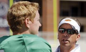 In this photo taken April 16, 2011, Oklahoma State offensive coordinator Todd Monken, right, talks to quarterback Brandon Weeden (3) during the Orange/White spring NCAA college football game at Boone Pickens Stadium in Stillwater, Okla., In Dana Holgorsen's only year as the offensive coordinator at Oklahoma State, the school's records for scoring and, more importantly, wins got broken. Now, Monken gets to pick up where Holgorsen left off. PHOTO BY NATE BILLINGS, The Oklahomam