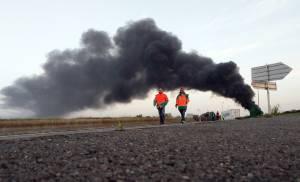 French dock workers throw smoke bombs as protests escalate