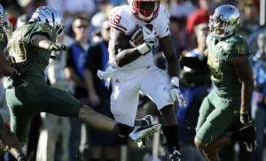 Wisconsin's Montee Ball, center, evades Oregon's John Boyett, left, and Michael Clay, right, during the first half of the Rose Bowl NCAA college football game, Monday, Jan. 2, 2012, in Pasadena, Calif. (AP Photo/Jae C. Hong)