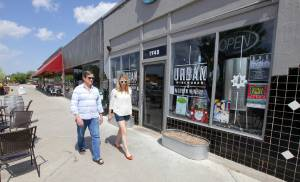 Developer Steve Mason and Kristen Vails, former executive director of the Plaza District Association,walkpast Urban Wineworks in the 1700 block of NW 16 of the Plaza District in this 2014 photo. The two are at odds with developers Jeff and Amiee Struble over how to deal with an unsightly property and the plan to add a shipping container converted into a snow cone stand to the corner of NW 16 and Blackwelder Avenue. [The Oklahoman Archives]