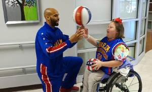 Harlem Globetrotter Hawk Thomas helps Bella Baldwin spin a basketball on her finger during a visit to The Children's Center Rehabilitation Hospital in Bethany. [Photo provided]