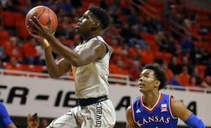 Oklahoma State's Jawun Evans, left, goes past Kansas' Devonte' Graham in the Cowboys' victory in January. Evans is listed as day to day going into Saturday's 1 p.m. game against Iowa State in Stillwater. (Photo by Bryan Terry, The Oklahoman)