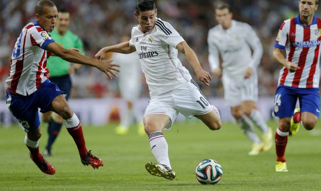 Real Madrid's James Rodriguez from Colombia duels for the ball with Atletico Madrid's Joao Miranda from Brazil, left, during a Spanish Super Cup soccer match at the Santiago Bernabeu stadium  in Madrid, Spain, Tuesday, Aug. 19, 2014 . (AP Photo/Daniel Ochoa de Olza)