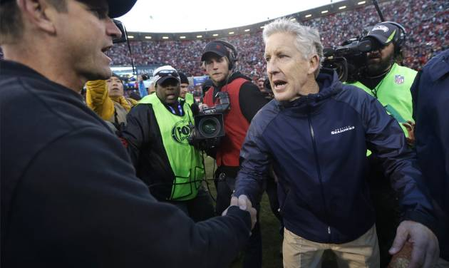 FILE - In this Dec. 8, 2013, file photo, San Francisco 49ers head coach Jim Harbaugh, left, shakes hands with Seattle Seahawks head coach Pete Carroll, right, after an NFL football game in San Francisco. The 49ers defeated the Seahawks 19-17. The Seahawks host the 49ers in the NFC championship on Sunday. (AP Photo/Marcio Jose Sanchez)