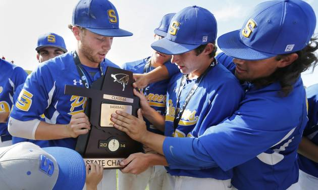 Stillwater players adjust the name plate on the Championship plaque after defeating  Bishop Kelley in the Class 6A high school baseball state championship final at L. Dale Mitchell Park on May 16, 2014 in Norman, Okla. Photo by Steve Sisney, The Oklahoman
