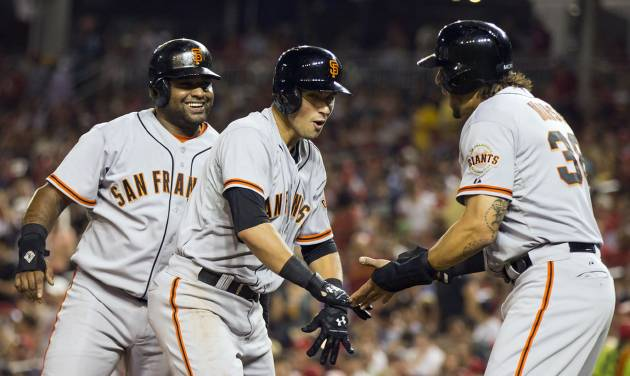 San Francisco Giants' Joe Panik, center, is congratulated by teammates Pablo Sandoval, left, and Michael Morse after hitting a three-run home run during the fourth inning of a baseball game against the Washington Nationals on Friday, Aug. 22, 2014, in Washington. (AP Photo/Evan Vucci)