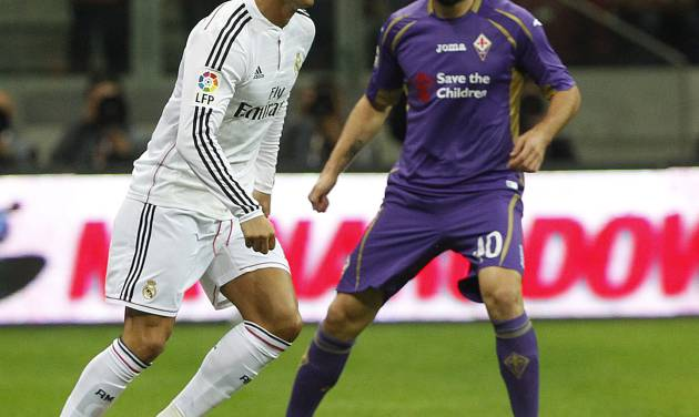 Real Madrid's Cristiano Ronaldo from Portugal, left, and Fiorentina's Borja Valero  challenge for the ball during their friendly soccer match  in Warsaw, Poland, Saturday, Aug. 16, 2014.(AP Photo/Czarek Sokolowski)