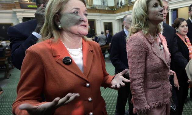 Sen. Sylvia Garcia, D-Houston, left, throws up her hands as she leaves the Senate Chamber with Sen. Wendy Davis, D-FortWorth, right, after the Texas Senate passed an abortion bill, Friday, July 12, 2013, in Austin, Texas. The bill will require doctors to have admitting privileges at nearby hospitals, only allow abortions in surgical centers, dictate when abortion pills are taken and ban abortions after 20 weeks. (AP Photo/Eric Gay)