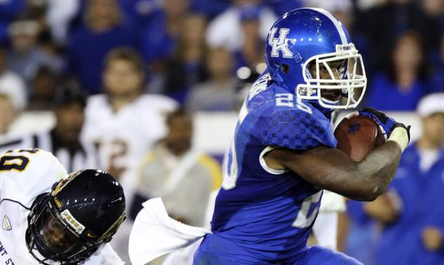 Kentucky's Jonathan George, right, eludes Kent State's Malcom Pannell (20) and Calvin Tiggle (8) for a touchdown during the third quarter of an NCAA college football game at Commonwealth Stadium in Lexington, Ky., Saturday, Sept. 8, 2012. Kentucky won 47-14. (AP Photo/James Crisp)