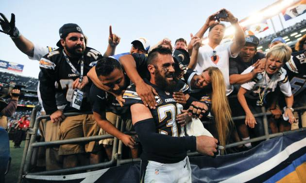 San Diego Chargers free safety Eric Weddle (32) is mobbed by fans after an NFL football game against the Kansas City Chiefs on Sunday, Dec. 29, 2013, in San Diego. The Chargers won 27-24 in overtime.  (AP Photo/Denis Poroy)