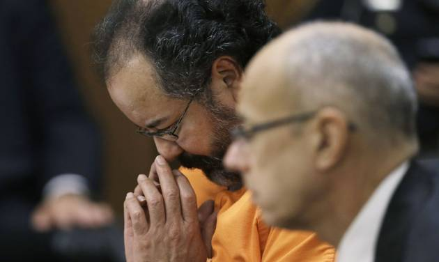 Ariel Castro looks down during court proceedings Friday, July 26, 2013, in Cleveland. Castro, who imprisoned three women in his home, subjecting them to a decade of rapes and beatings, pleaded guilty Friday to 937 counts in a deal to avoid the death penalty. Defense attorney Jaye Schlachet is on the right. (AP Photo/Tony Dejak)