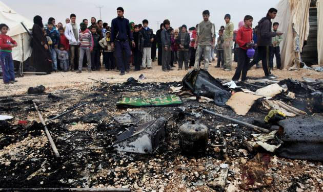 Syrian refugees look at remains of a burnt tent at Zaatari Syrian refugees camp, in Mafraq, near the Syrian border, Jordan, Monday, Jan. 28, 2013. A refugee tent caught on fire, and the family who lives in it was evacuated by the refugees. (AP Photo/Mohammad Hannon)