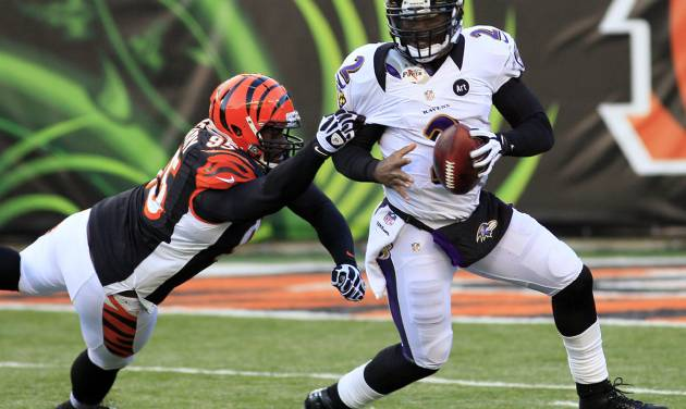 Baltimore Ravens quarterback Tyrod Taylor (2) is pursued by Cincinnati Bengals defensive end Wallace Gilberry (95) in the second half of an NFL football game, Sunday, Dec. 30, 2012, in Cincinnati. The Bengals won 23-17. (AP Photo/Tom Uhlman)
