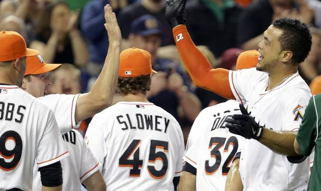 Miami Marlins' Giancarlo Stanton, right, high-fives manager Mike Redmond, left, after hitting a grand slam to defeat the Seattle Mariners 8-4 during the ninth inning of an interleague baseball game on Friday, April 18, 2014, in Miami. (AP Photo/Lynne Sladky)