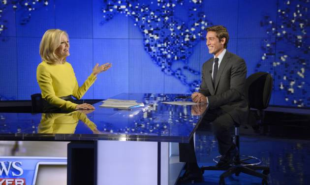 """In this Wed., Aug. 27, 2014 photo provided by ABC, Diane Sawyer, left, signs off on her last broadcast as anchor of """"World News,"""" with new anchor, David Muir, right, looking on in New York. Among the stories Muir will introduce during his first week as ABC's """"World News"""" anchor in early September, is one he reported about a generation of Syrian refugees missing out on an education.  (AP Photo/ABC, Ida Mae Astute, file)"""
