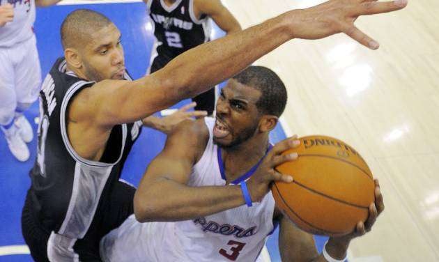 Los Angeles Clippers guard Chris Paul, right, puts up a shot as San Antonio Spurs center Tim Duncan defends during the second half in Game 4 of an NBA basketball playoffs Western Conference semifinal, Sunday, May 20, 2012, in Los Angeles. The Spurs won 102-99. (AP Photo/Mark J. Terrill)