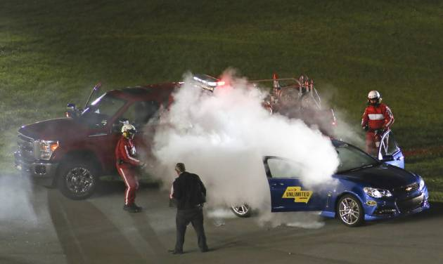 Track workers extinguish a fire that started in the pace car during the NASCAR Sprint Unlimited auto race at Daytona International Speedway in Daytona Beach, Fla., Saturday, Feb. 15, 2014. (AP Photo/Jim Topper)