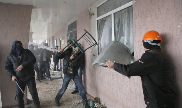 Pro-Russian men storm a police station in the eastern Ukrainian town of Horlivka on Monday, April 14, 2014.  Several government buildings have fallen to mobs of Moscow loyalists in recent days as unrest spreads across the east of the country. (AP Photo/Efrem Lukatsky)