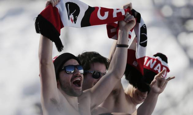 Canadian fans cheer during the men's ski slopestyle qualifying at the Rosa Khutor Extreme Park, at the 2014 Winter Olympics, Thursday, Feb. 13, 2014, in Krasnaya Polyana, Russia. (AP Photo/Andy Wong)