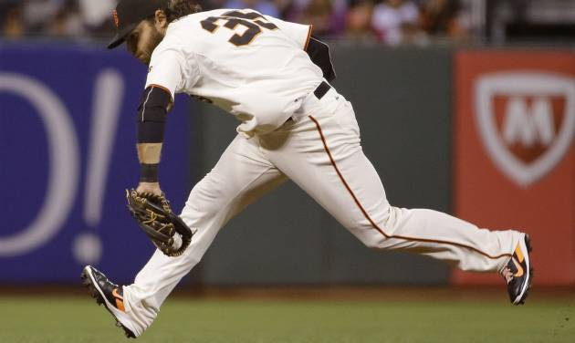 San Francisco Giants shortstop Brandon Crawford stops a ground ball hit by St. Louis Cardinals' Matt Holliday in the sixth inning of a baseball game Wednesday, July 2, 2014, in San Francisco. Crawford made the throw and Holliday was out at first base on the play. (AP Photo/Eric Risberg)