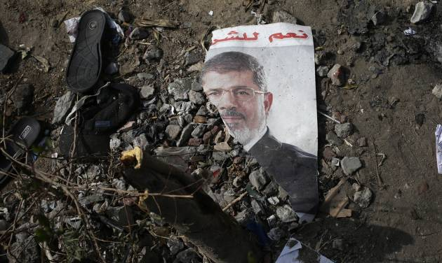 """FILE - In this Friday, Aug. 16, 2013 file photo, a trampled poster of Egypt's ousted President Mohammed Morsi is seen on the ground outside the Rabaah al-Adawiya mosque, where supporters of Morsi had a protest camp in Nasr City, Cairo, Egypt. Arabic reads, """"Yes for the legitimacy."""" Almost a quarter-century ago, a young American political scientist achieved global academic celebrity by proclaiming that the collapse of communism had ended the discussion on how to run societies, leaving """"Western liberal democracy as the final form of human government."""" In Egypt and around the Middle East, after a summer of violence and upheaval, the discussion, however, is still going strong.  And almost three years into the Arab Spring revolts, profound uncertainties remain. (AP Photo/Hassan Ammar, File)"""