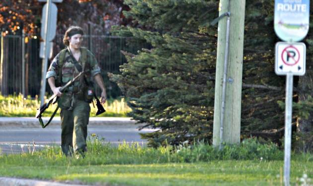 A heavily armed man that police have identified as Justin Bourque walks on Hildegard Drive in Moncton, New Brunswick, on Wednesday, June 4, 2014, after several shots were fired in the area. The man, suspected of killing three Royal Canadian Mounted Police officers, was spotted three times Thursday but has so far eluded a massive manhunt, police said. (AP Photo/The Canadian Press, Moncton Times & Transcript, telegraphjournal.com, Viktor Pivovarov) MANDATORY CREDIT