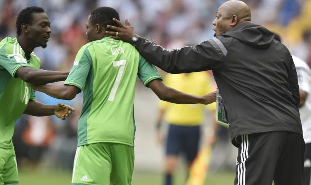 Nigeria's coach Stephen Keshi, right, and teammate Juwon Oshaniwa, left, congratulate Ahmed Musa after he scored his side's second goal during the group F World Cup soccer match against Argentina at the Estadio Beira-Rio in Porto Alegre, Brazil, Wednesday, June 25, 2014. (AP Photo/Martin Meissner)