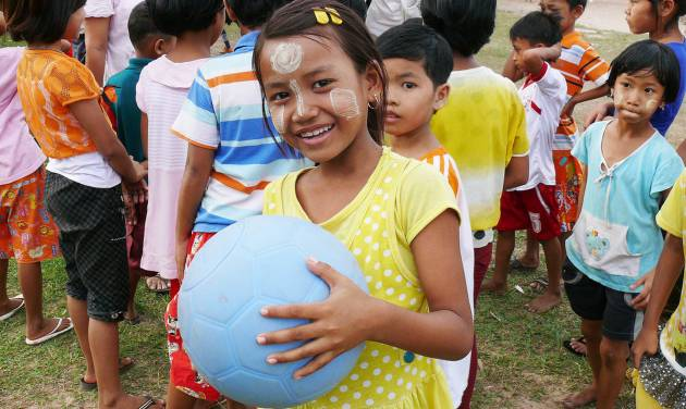 In this November 2013 photo provided by the One World Futbol Project, a school girl holds a blue One World Futbol at a school in Mawlamyine, Myanmar. The ball was part of a larger donation of 5,000 plus balls to the country. When Lisa Tarver and husband Tim Jahnigen set out four years ago to distribute their indestructible blue soccer balls to areas in need across the world, little did they know how far the project would evolve in just four years, in the span of a single World Cup cycle. Their One World Futbol project has shipped more than 850,000 soccer balls to organizations worldwide, touching the lives of some 30,000,000 children, many of whom would never have had access to such equipment or would have come up with their own version of a ball. (AP Photo/One World Futbol Project)