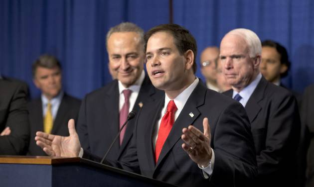 """FILE – In this April 18, 2013, file photo Sen. Marco Rubio, R-Fla., speaks at a Capitol Hill news conference with the Senate's """"Gang of Eight"""", the bipartisan team pushing an immigration overhaul, to outline their immigration reform legislation that would creates a path for 11 million unauthorized immigrants to apply for U.S. citizenship. After radio host Rush Limbaugh told Rubio many conservatives """"are scared to death"""" that the Republican Party """"is committing suicide, that we're going to end up legalizing 9 million automatic Democrat voters,"""" Rubio said the risk is worth taking. """"Every political movement, conservatism included, depends on the ability to convince people that do not agree with you now to agree with you in the future,""""he said. At right is Republican Sen. John McCain of Arizona, and at Rubio's left is Democrat Sen. Chuck Schumer of New York. (AP Photo/J. Scott Applewhite, File)"""