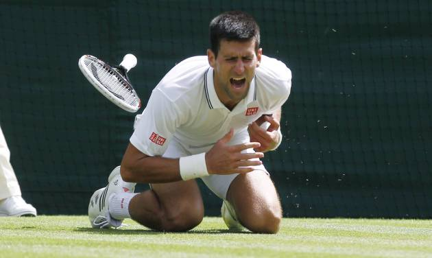 Novak Djokovic of Serbia shouts in pain after falling onto the court during the men's singles match against Gilles Simon of France at the All England Lawn Tennis Championships in Wimbledon, London, Friday, June 27, 2014. (AP Photo/Sang Tan)