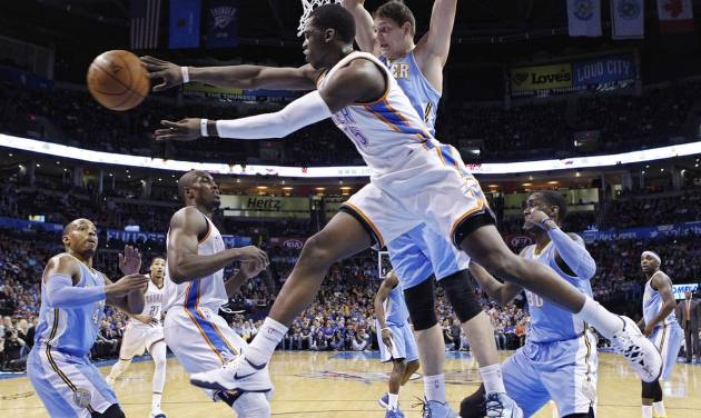 Oklahoma City Thunder guard Reggie Jackson (15) passes from under the basket in front of Denver Nuggets center Timofey Mozqov (25) in the first quarter of an NBA basketball game in Oklahoma City, Monday, March 24, 2014. (AP Photo/Sue Ogrocki)