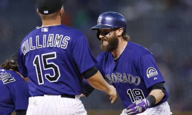 Colorado Rockies' Charlie Blackmon, right, celebrates his walkoff, RBI-single with teammates Charlie Culberson, left, and Jackson Williams against the San Francisco Giants in the ninth inning of the Rockies' 10-9 victory in a baseball game in Denver on Monday, Sept. 1, 2014. (AP Photo/David Zalubowski)