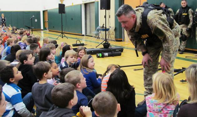 FILE - In this file photo of Jan. 28, 2013, Capt. Bryn Reynolds of the Washington County Sheriff's Office takes a question from a student at the Hudson Falls Primary School in Hudson Falls, N.Y. Reynolds and other officers were present to show off their equipment and discuss safety and to practice drills with unloaded guns to prepare for armed intruders at the school. School security has come under more scrutiny in the wake of the Sandy Hook Elementary School massacre in Newtown, Conn., that killed 26 people in December. (AP Photo/The Post-Star, Omar Ricardo Aquije, File)