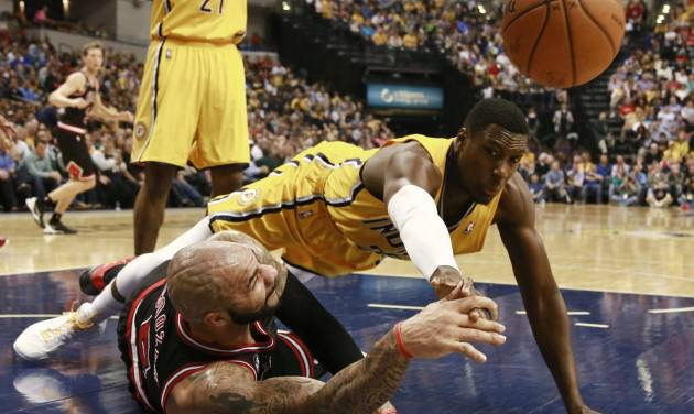 CORRECTS SPELLING OF BOOZER - Chicago Bulls forward Carlos Boozer, left, passes the basketball as Indiana Pacers center Ian Mahinmi dives for it in the first half of an NBA basketball game in Indianapolis, Friday, March 21, 2014. (AP Photo/R Brent Smith)