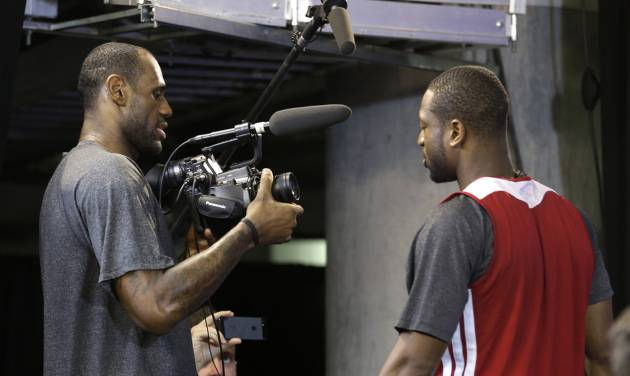 Miami Heat small forward LeBron James, left, points a video camera at shooting guard Dwyane Wade after a news conference following basketball practice on Saturday, June 8, 2013, at the American Airlines Arena in Miami. The Heat and the San Antonio Spurs are to play Game 2 of the NBA Finals, Sunday. (AP Photo/Wilfredo Lee)