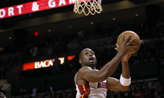 Miami Heat's Dwyane Wade (3) goes to the basket as Milwaukee Bucks' Ersan Ilyasova, left, defends during the first half of an NBA basketball game, Wednesday, Nov. 21, 2012, in Miami. (AP Photo/Alan Diaz)