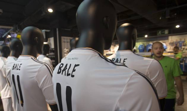 Welsh soccer international Gareth Bale soccer shirts are displayed in the official Real Madrid shop in Madrid, Monday, Sept. 2, 2013. Real Madrid earlier presented Gareth Bale to tens of thousands of fans at the Santiago Bernabeu stadium after the Wales international passed a medical test earlier on Monday. Bale became football's most expensive transfer at euro 100 million ($132 million) after a long-running transfer saga that spanned most of the summer. (AP Photo/Paul White)