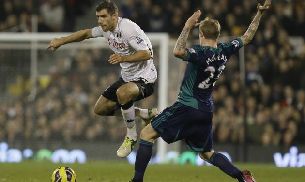 Fulham's Aaron Hughes, left, jumps over a tackle by Sunderland's James McClean during their English Premier League soccer match at Fulham's Craven Cottage stadium in London, Sunday Nov. 18, 2012. (AP Photo/Alastair Grant)