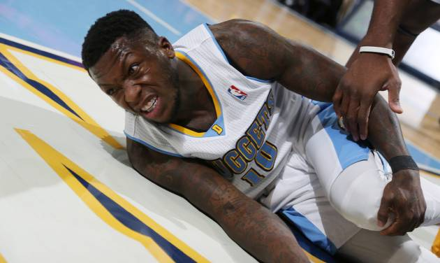 Denver Nuggets guard Nate Robinson grimaces as he holds his knee after being injured while defending a shot against the Charlotte Bobcats in the first quarter of an NBA basketball game in Denver on Wednesday, Jan. 29, 2014. Robinson left the game shortly after the play. (AP Photo/David Zalubowski)