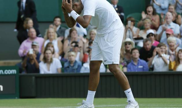 Nick Kyrgios of Australia holds his head after defeating Rafael Nadal of Spain in their men's singles match on Centre Court at the All England Lawn Tennis Championships in Wimbledon, London, Tuesday, July 1, 2014. (AP Photo/Ben Curtis)