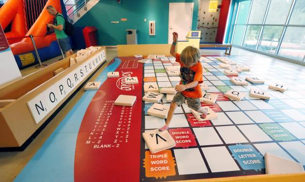 In this July 3, 2014 photograph, Maston Johnson, 5, from Tampa, Fla., leaps through the oversized Scrabble board after spelling out his name, at the Mississippi Children's Museum in Jackson, Miss. The interactive hands-on facility promotes literacy, health and nutrition, learning the state's heritage and exploration of its cultural arts and key economic industries in a fun setting. (AP Photo/Rogelio V. Solis)