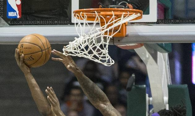 Milwaukee Bucks' Brandon Knight shoots a reverse lay-up as Los Angeles Lakers' Jordan Hill defends during the first half of an NBA basketball game Thursday, March 27, 2014, in Milwaukee. (AP Photo/Tom Lynn)