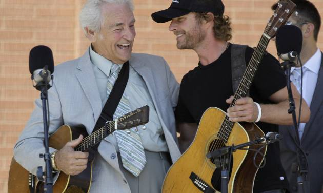 Country music star Dierks Bentley gets a hug from bluegrass star Del McCoury, left, after they performed at a free, outdoor concert in downtown Nashville, Tenn., on Tuesday, Sept. 27, 2011, during the week-long International Bluegrass Music Association celebration. (AP Photo/Mark Humphrey)