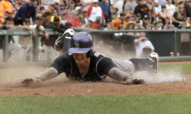 Colorado Rockies' Brandon Barnes slides home on his two-run inside-the-park home run off San Francisco Giants pitcher Sergio Romo during the ninth inning of a baseball game in San Francisco, Saturday, June 14, 2014. (AP Photo/Jeff Chiu)