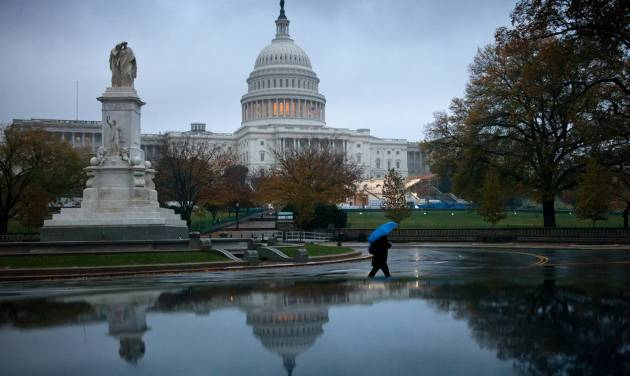 FILE - In this Nov. 13, 2012 file photo, a man walks in front of the Capitol in Washington. The debate in Washington over taxes and spending is likely to continue damaging the fragile economy well into 2013. The political standoff has already taken an economic toll, creating uncertainty about the future and discouraging consumers from spending and businesses from hiring and investing. (AP Photo/J. Scott Applewhite, File)