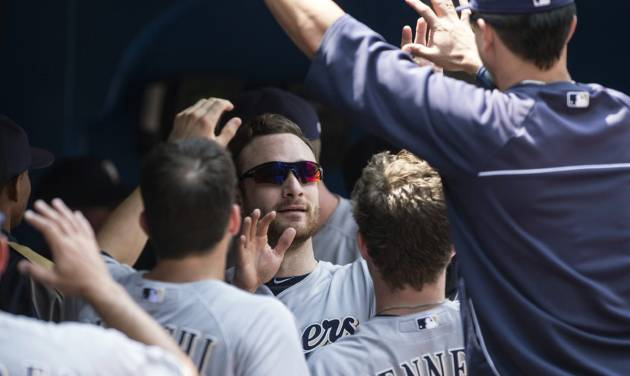 Milwaukee Brewers Jonathan Lucroy, center, celebrates after scoring on a single by Carlos Gomez during first inning interleague baseball action against the Toronto Blue Jays in Toronto on Wednesday July 2 , 2014. (AP Photo/The Canadian Press, Chris Young)