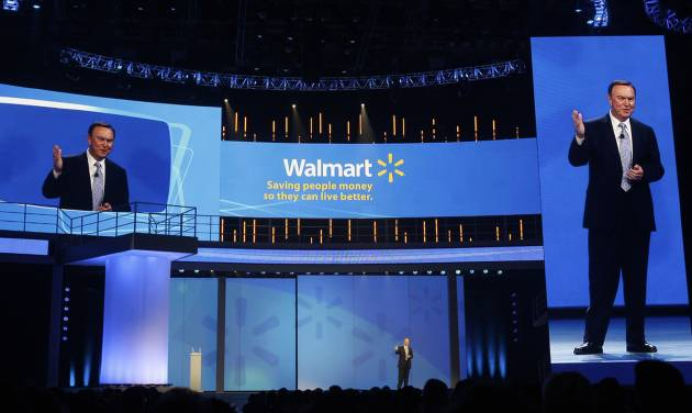 Mike Duke, President and CEO of Wal-Mart, center, speaks to shareholders as his image appears on screens left and right in Fayetteville, Ark., Friday, June 3, 2011. (AP Photo/Danny Johnston)