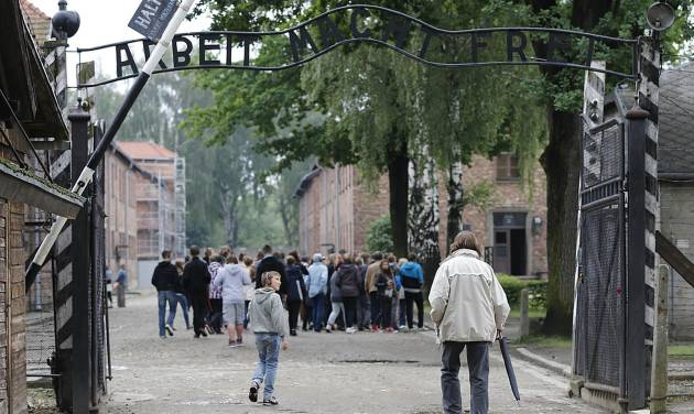 FILE- Tourists visit the former Nazi death camp of Auschwitz in Oswiecim, Poland, in this file photo dated Wednesday, June 6, 2012.  The Auschwitz-Birkenau memorial site in southern Poland registered 1.43 million visitors last year, a record number in its 65-year history as a place of Holocaust remembrance, officials said Friday Jan 4, 2013. (AP Photo/Gregorio Borgia, File)
